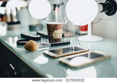 A Cup Of Coffee And A Make-up Brush On The Master's Desk In The Backlight