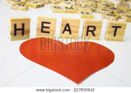 Word Heart. Wooden Letters Spelling The Word Heart On White Background. One Red Heart.