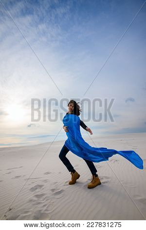 Beautiful Young Woman, Wearing In A Flying Blue Scarf, Is Dancing In The Desert On The Wind - On The