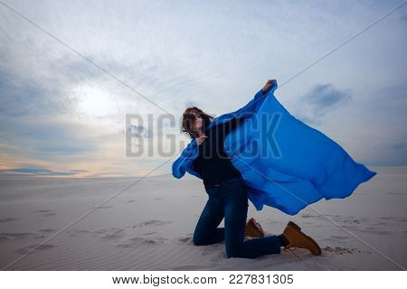Joyful Girl, Wearing In A Flying Blue Scarf, Fights The Wind In The Desert - On The Beginning Of Sto