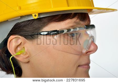 Woman With Protective Ear Plugs And Helmet