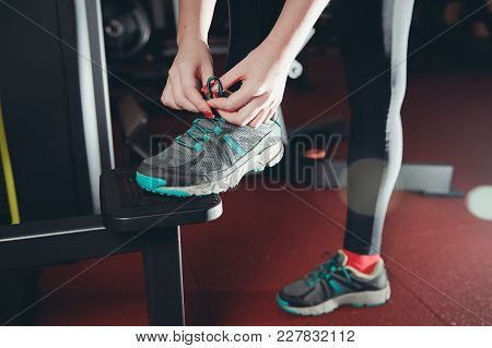 Close-up Of Girl Tying Shoelaces On Sports Shoes In Gym.