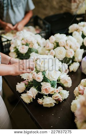 Two Florists Arranging Flowers For Wedding Day