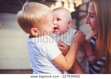 Woman Mother With Two Young Children Entertain Girl Embrace, Concept Maternity And Parenting