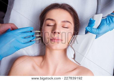 Beauty Injection. Closeup Of Doctor Hands With Syringe Near Female Face. Portrait Of Beautiful Woman