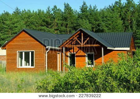 Wooden House In Countryside. Ecological Small Wooden House. Wooden House With Meadow In Front Of It.
