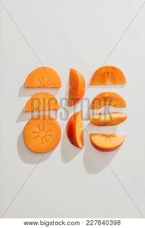 Top View Of Persimmons Pieces In Rows On White Tabletop