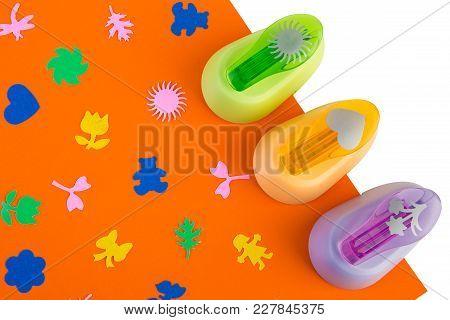 Three Figure Staplers On Orange Paper, Staplers For Creativity