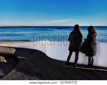 A Picture Of The Beach And Two Women Looking At The Sea.