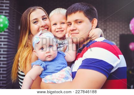 Happy Young Family With Children, Parents And Children On The Background Of Their Own Home, Family H