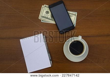 Cup Of Coffee, Smartphone, Dollars, Notepad And Pen On Wooden Desk