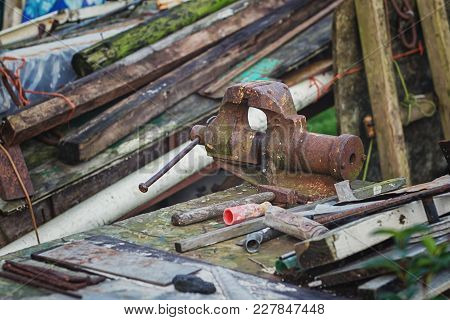 Rusted Vise And Hammer Between The Waste Wood