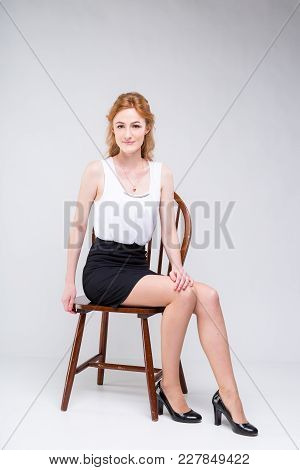 Portrait Of Beautiful Business Woman With Long Red, Curly Hair Sitting On Wooden Chair On White Back