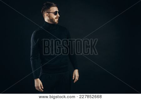 Bearded Man In Elegant Black Turtleneck And Flip Sunglasses Standing With Confidence On Black.