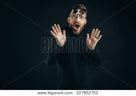 Young Bearded Man In Black Looking With Surprise At Camera Wearing Round Flip-up Glasses On Black.
