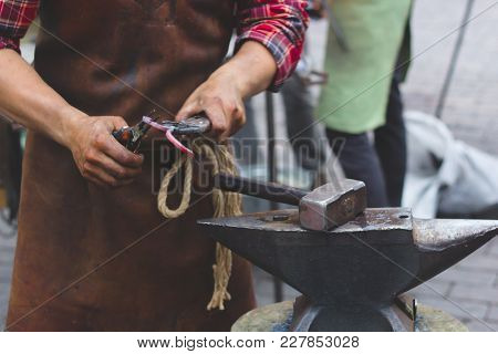 The Blacksmith Manually Forging The Molten Metal On The Anvil In Smithy. Branding Irons In Campfire
