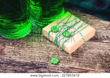 St. Patrick's Day Background With Two Mugs Of Green Beer, Snack And Gift Box For Celebration.