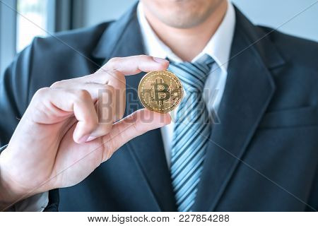 The Businessman Are Showing Gold Bitcoin. Crypto Currency Is Being Widely Used Around The World.