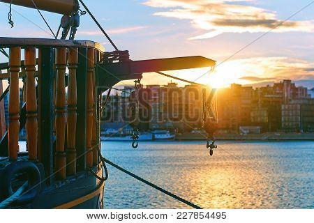 Winch With Hooks On The Stern Of A Wooden Ship In The Evening Port With Modern Cityscape On Backgrou