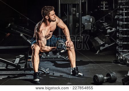Athletic Man Bodybuilder Execute Exercise With Dumbbells For Biceps And Sitting In Dark Gym Looking