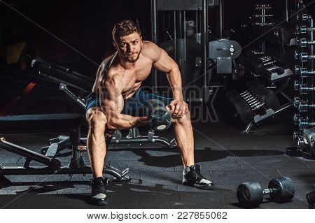 Athletic Man Bodybuilder Execute Exercise With Dumbbells For Biceps And Sitting In Dark Gym