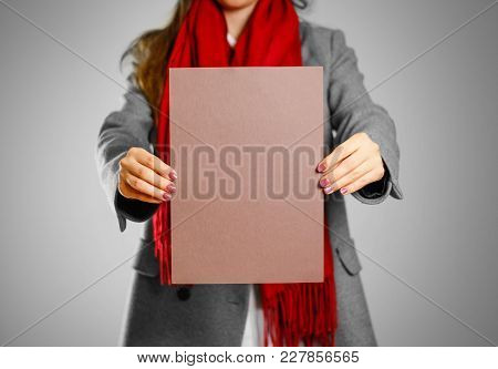 A Girl In Grey Coat And Red Scarf Keeps A Brown Clean Blank Sheet Of A4. Isolated On Grey Background