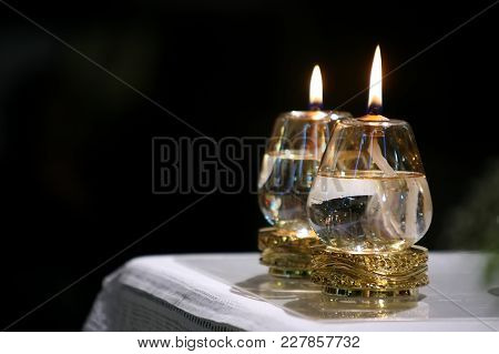 Two Burning Church Candles On The Table