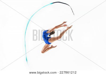 The Portrait Of Beautiful Young Brunette Woman Gymnast Training Calilisthenics Exercise With Blue Ri