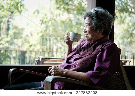 Asian Elder Woman Holding Tea Cup On Terrace. Elderly Female Relaxing On Patio. Senior Drinking Coff