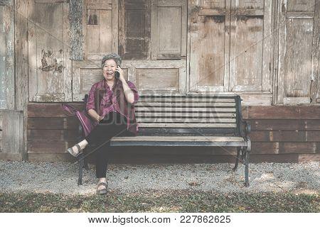 Elder Woman Talk On Mobile Phone In Garden. Elderly Female Speaking On Smartphone In Park. Asian Sen