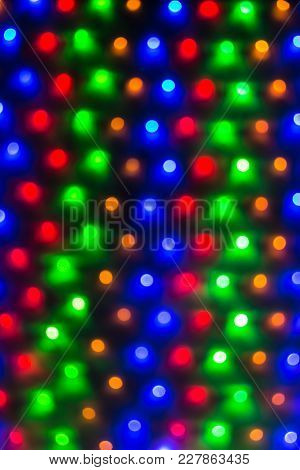 Abstract Image Of Many Defocused Varicolored Round Lights In A Row Closeup