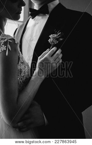 Bride Dresses The Boutonniere To The Groom