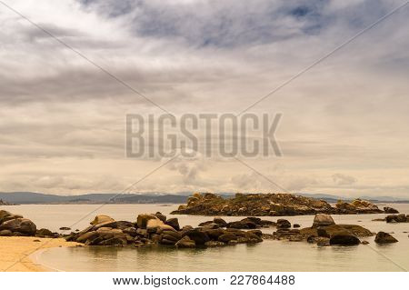 Rocks At East Corner Of Coroso Beach, In Riveira, Galicia (spain) On A Cloudy Day. Island Of Illa Do