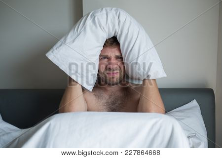 Caucasian Man Suffering From Insomnia And Shutting Ears With Pillow.