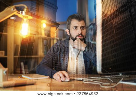 Thoughtful Man. Clever Responsible Worker Of A Big Company Looking Thoughtful While Sitting In Front