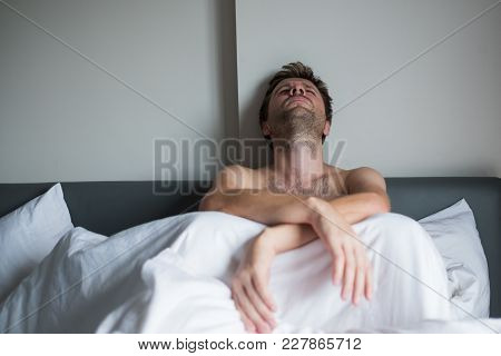 Portrait Of An Upset Young Man Sitting On A Bed Alone. He Break Up With His Girlfriend And Now Is Mi