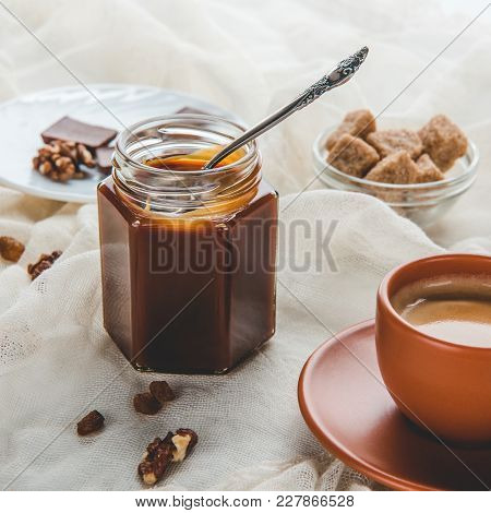 Appetizing Jar Of Caramel Jam And Cup Of Coffee On Tablecloth