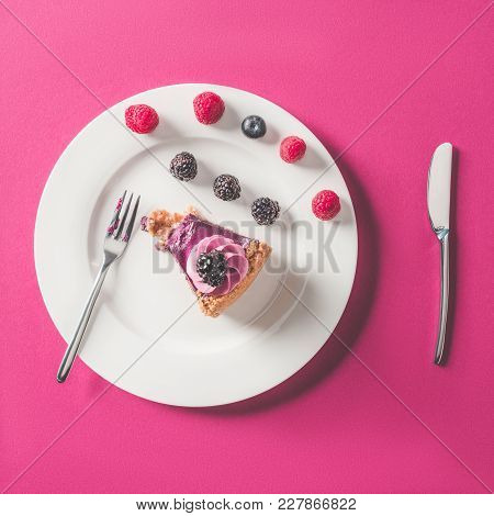 Top View Of Bitten Piece Of Cake With Berries On Plate On Pink Surface