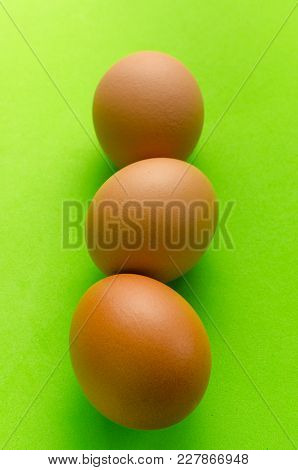 Three Brown Eggs On A Bright Green Background.