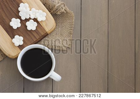 Top View Of Some White Coconut Tapioca Cookies Spread On A Wooden Block And A Cup Of Coffee.