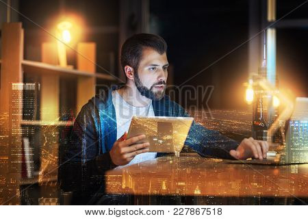 Two Devices. Attentive Young Bearded Man Sitting At The Table And Looking At The Screen Of A Compute