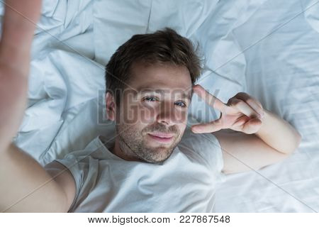 Handsome Man In White Shirt Taking A Selfie In Bed Saying Hello To His Girlfriend In The Morning
