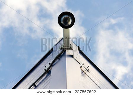 Modern Dome Security Camera Attached To Wall With Blue Clear Sky Background Copy Space Low Angle Vie