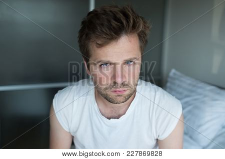 Serious Pensive Man Looking At Camera Sitting On Bed. Concept Of Bad Morning At Home Alone