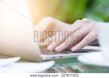 Asian Woman Hands Has Touching And Typing On Laptop Computer With Blurred Coffee, Computer And View