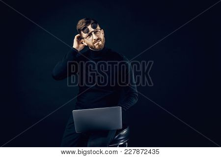 Elegant Man In Black Clothes And Flip-up Glasses Brainstorming On Idea Sitting With Laptop.