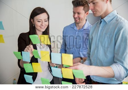 Smiling Male And Female Business Professionals Sticking Notes On Glass In Office
