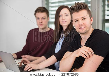 Portrait Of Confident Businessman With Female Colleague In Office