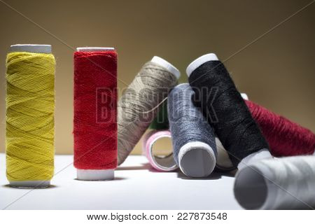 Background With A Lot Of Colorful Coils With Threads. Bobbins Are Stacked In Three Rows, One On The