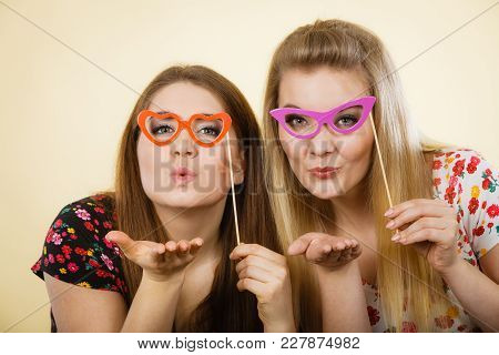 Two Happy Women Holding Fake Eyeglasses On Stick Having Fun Wearing Tshirts With Flower Pattern. Pho